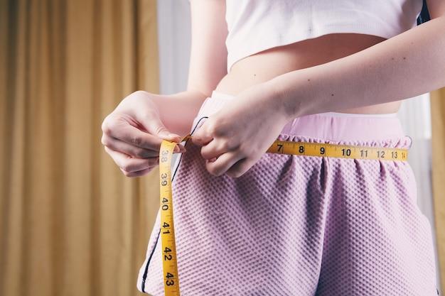 Donna che misura la sua vita con nastro adesivo di misurazione