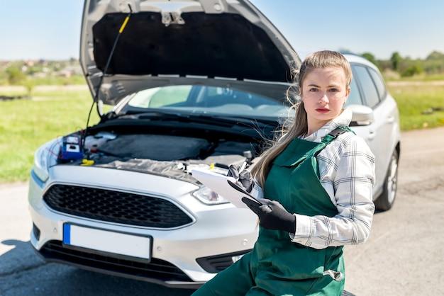 Meccanico donna che prende appunti durante la diagnosi dell'auto