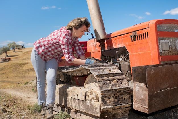Meccanico della donna che ripara un trattore nella campagna