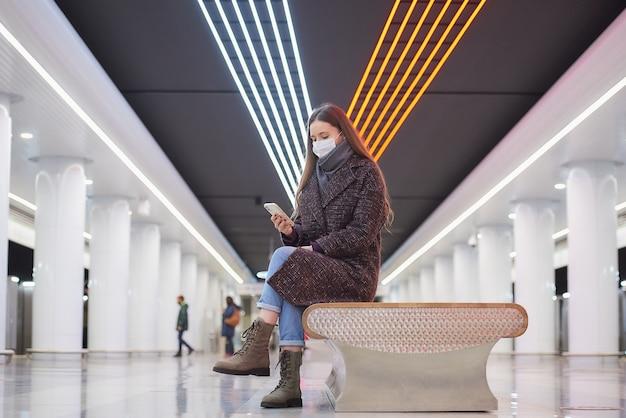 Una donna con una maschera medica è seduta al centro della grande stazione della metropolitana con uno smartphone e sta leggendo le notizie