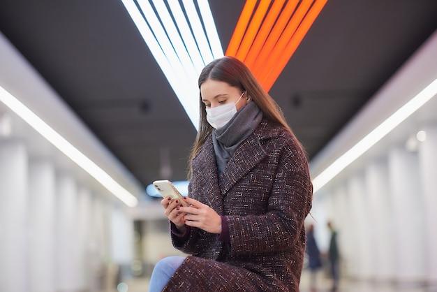 Una donna con una maschera medica è seduta al centro della banchina della metropolitana con uno smartphone e sta leggendo le notizie