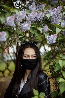 Donna in una mascherina medica su uno sfondo di lillà in fiore. maschera nera. protezione da virus, influenza. protezione dal coronavirus. allergia primaverile