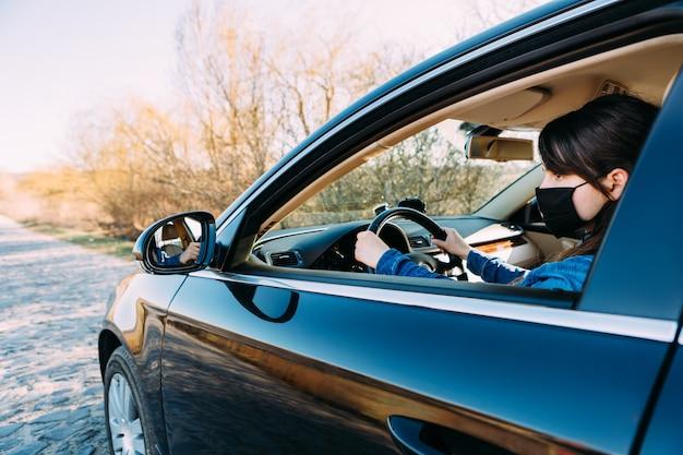Donna nella mascherina medica in automobile. coronavirus, malattia, infezione, quarantena, covid-19