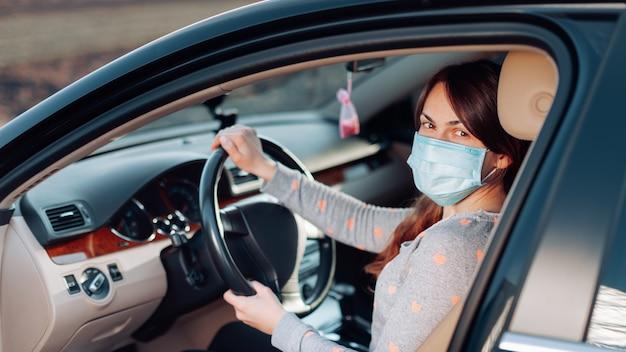 Donna nella mascherina medica in auto. coronavirus, malattia, infezione, quarantena, covid-19 Foto Premium