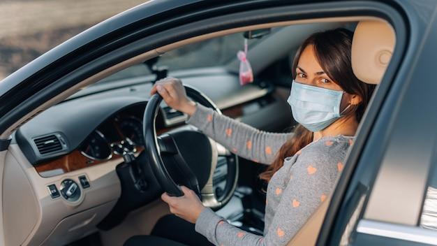 Donna nella mascherina medica in auto. coronavirus, malattia, infezione, quarantena, covid-19