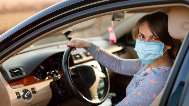 Donna nella maschera medica in auto. coronavirus, malattia, infezione, quarantena, covid-19