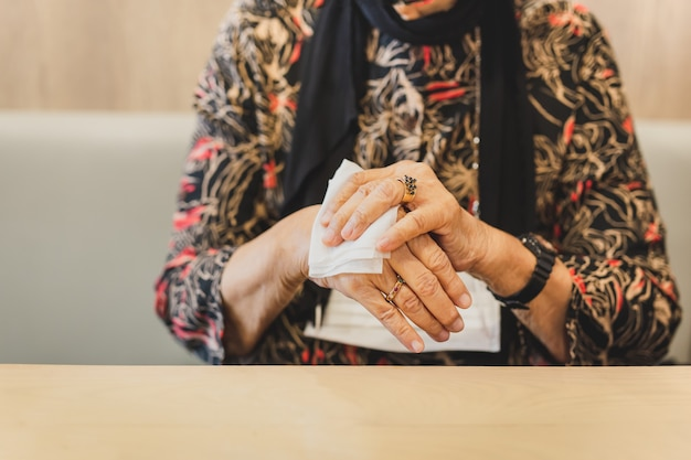 Donna in mascherina medica che pulisce le sue mani con salviettine umidificate.