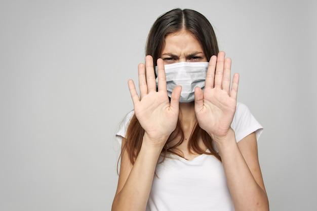 La donna in una mascherina medica tiene le sue mani davanti al suo sfondo chiaro stile di vita salute