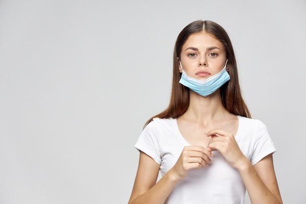 Una donna in una mascherina medica tiene le sue mani davanti alla sua maglietta bianca guarda avanti sfondo chiaro salute