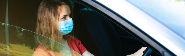 La donna in maschera medica sta guidando l'auto. tempo di coronavirus. situazione pericolosa.