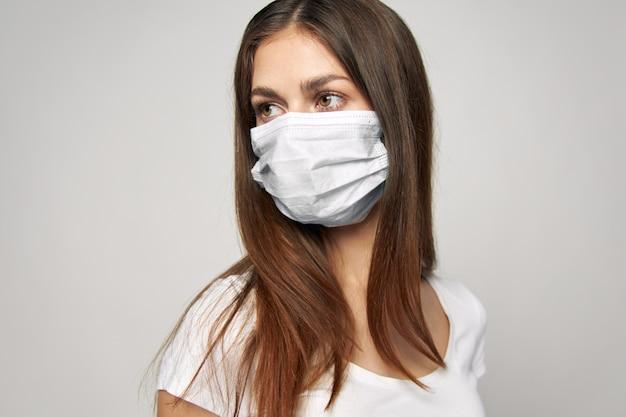 Donna in maschera medica guarda la maglietta bianca laterale