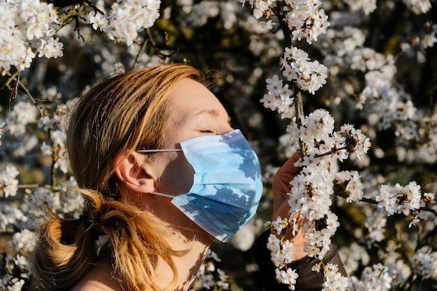 Donna in una mascherina medica vicino ad un ciliegio sbocciante. concetto di allergia e quarantena. Foto Premium