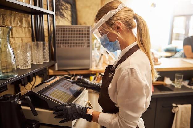 Donna in maschera medica e scudo di plastica che lavora su un registratore di cassa in una caffetteria