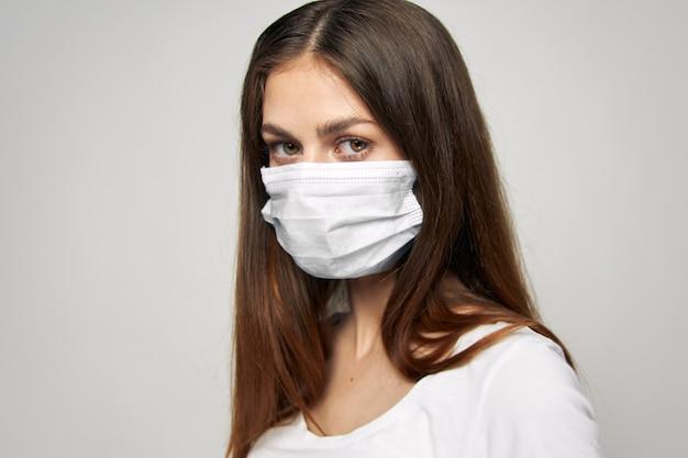 La donna in una polizia di mascherina medica guarda avanti il primo piano bianco della maglietta dei capelli lunghi