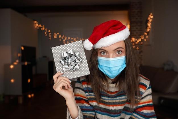 Donna in maschera medica e cappello da babbo natale dimostrando confezione regalo mentre si celebra il natale a casa durante la pandemia
