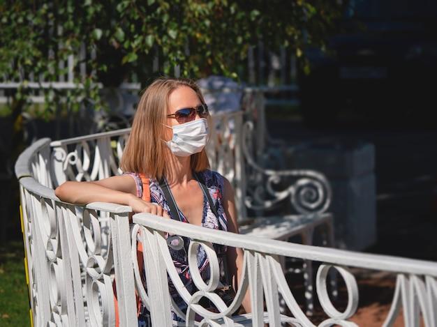 Donna in una maschera medica seduta su una panchina