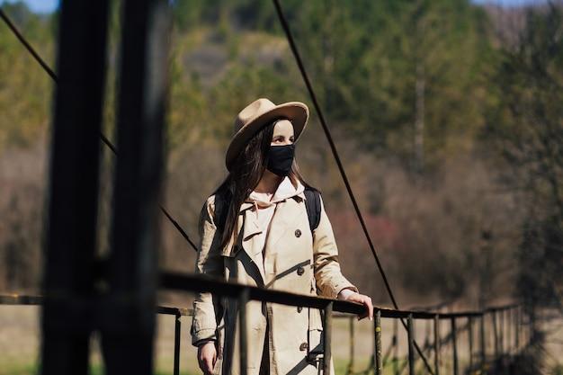 Donna in mascherina medica sul ponte sospeso nella foresta durante un viaggio