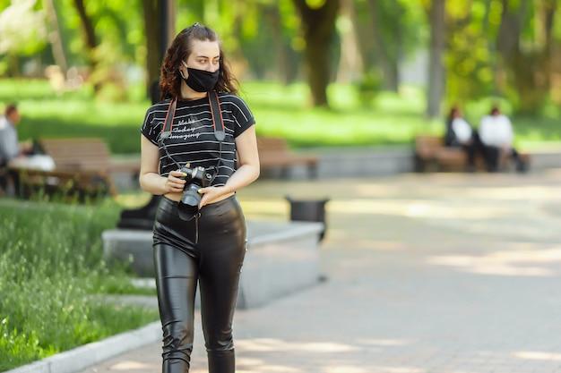 La donna in una mascherina medica cammina nel parco con una macchina fotografica