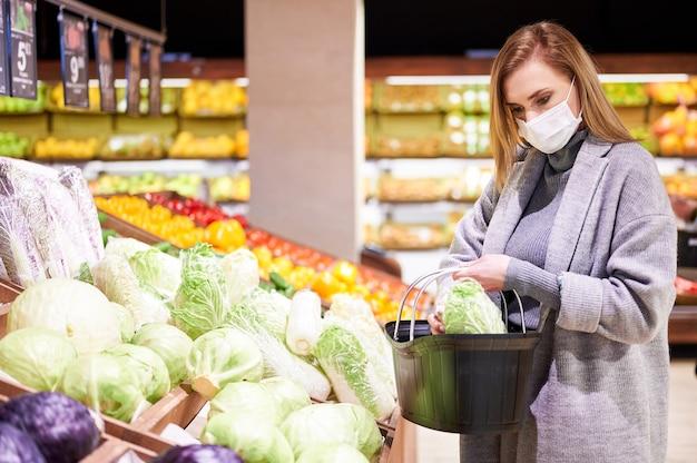 La donna in maschere mediche sta facendo la spesa in drogheria durante la pandemia di virus