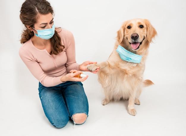 La donna nella mascherina protettiva medica disinfetta le zampe dei cani con un disinfettante