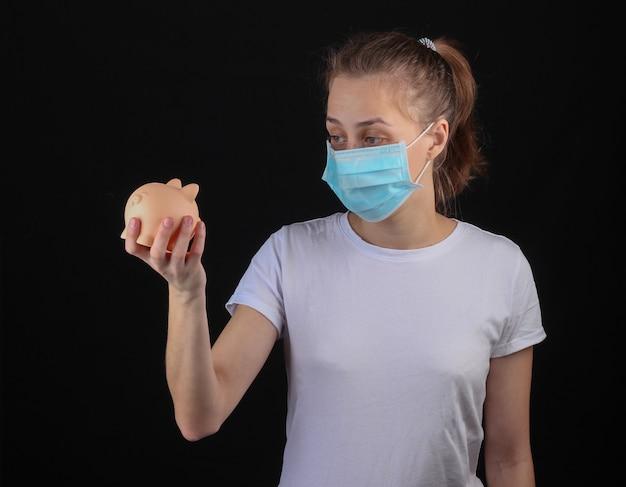 Donna in una maschera protettiva medica che tiene salvadanaio su una parete nera. crisi mondiale da covid-19