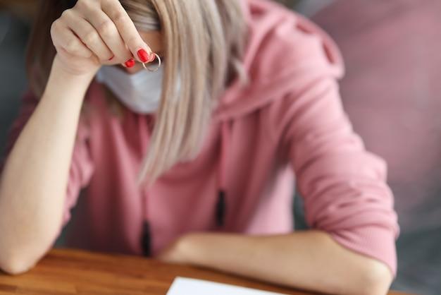 La donna nella mascherina protettiva medica si siede con la sua testa in giù e tiene la fede nuziale