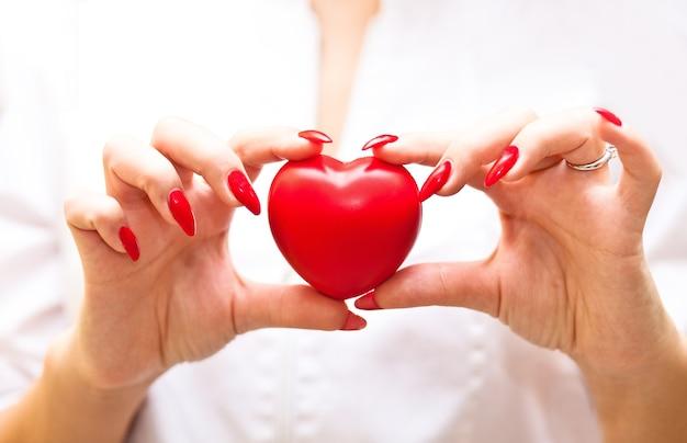 Donna in uniforme medica o vestito bianco che tiene un cuore in una mano.