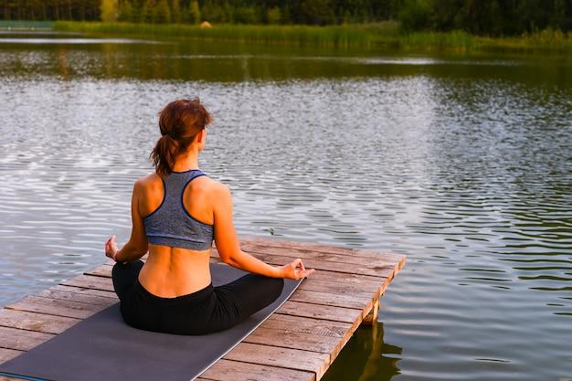 Una donna medita nella natura in riva al lago. il concetto di realizzare il significato della vita.