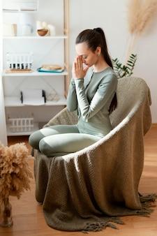 Donna che medita a casa sulla sedia
