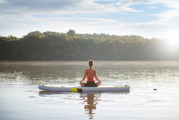 Donna meditando e praticando yoga durante l'alba in paddle board