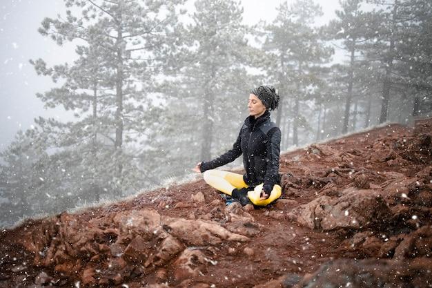 Donna meditando e praticando yoga in cima alla montagna