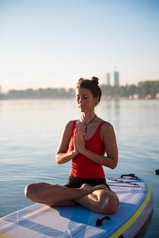 Donna meditando e praticando yoga durante l'alba su un paddleboard