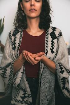 Donna che medita con le mani sotto forma di offerta vestita con un poncho fatto a mano