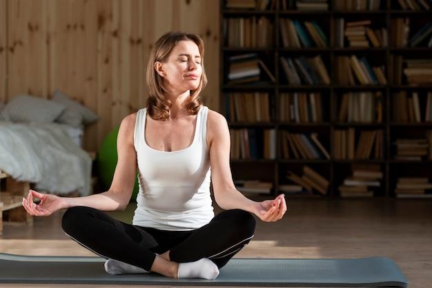 Donna che medita su stuoia di yoga