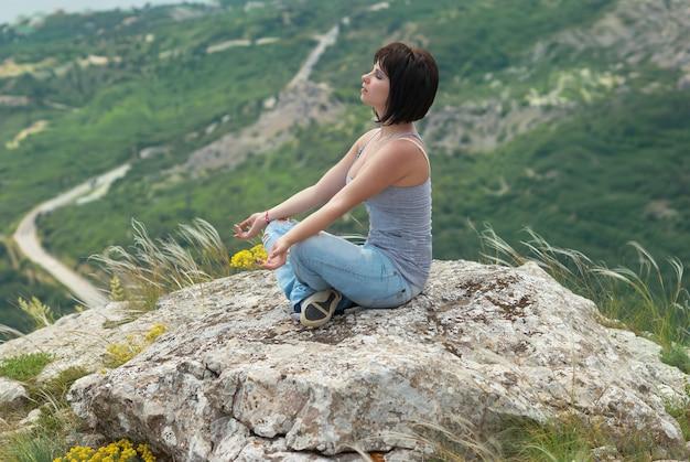 Donna in meditazione, rilassante sulla roccia