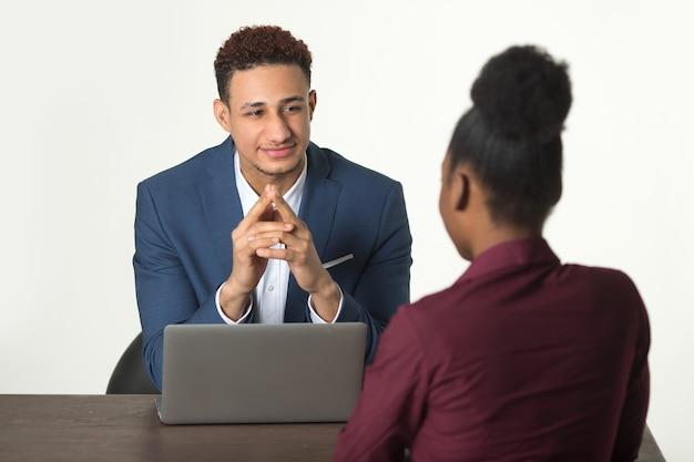 Donna in una riunione con un uomo al tavolo con un laptop