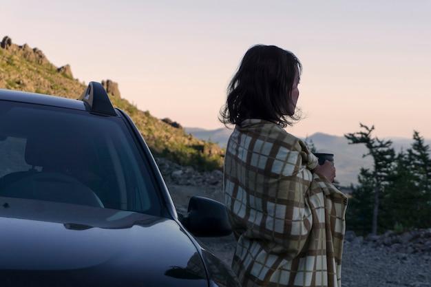 Una donna incontra l'alba con una tazza di caffè in mano in una selvaggia zona montuosa vicino alla macchina