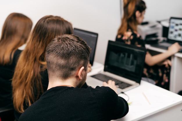 Una donna e uomini, grafici e architetti, che lavorano insieme nell'ufficio progetti