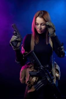 La donna in uniforme militare softair con un fucile automatico americano e una pistola su uno sfondo scuro
