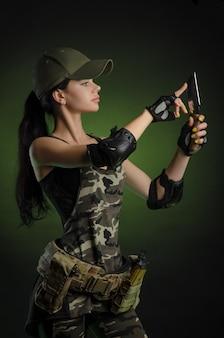 Donna in abiti speciali militari in posa con una pistola in mano su un muro scuro nella foschia