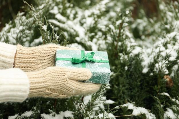 Donna in guanti che tengono il contenitore di regalo verde di natale all'aperto