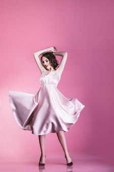 Modello di donna bella e alla moda in abito rosa su sfondo rosa