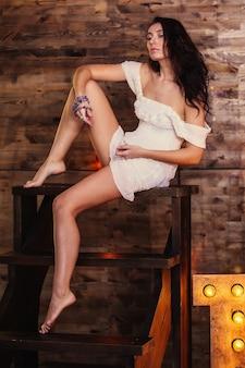 Modello di donna bella e alla moda abito bianco corto si siede su una scala di legno in studio, sullo sfondo di una parete in legno.foto verticale
