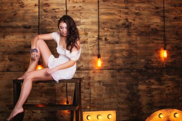 Abito bianco corto bella e alla moda bruna modello donna si siede su una scala di legno in studio