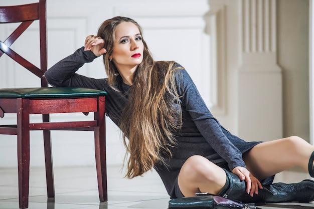 Modello di donna in abito con stivali alla moda e labbra rosse luminose in interni d'epoca