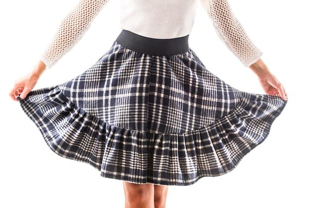 Il modello della donna tiene nelle sue mani la sua bella posa della gonna scozzese. concetto di abbigliamento casual da donna. spazio pubblicitario