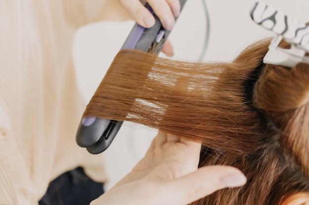 La modella della donna si sta vestendo i capelli dal parrucchiere nella stanza dello studio