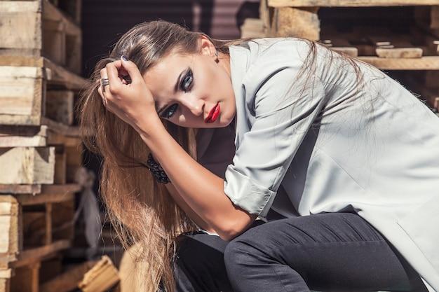 Modello di donna con trucco luminoso e labbra rosse in una giacca alla moda sullo sfondo di casse di legno