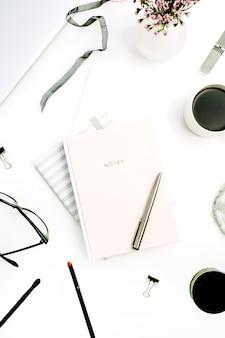 Donna moderna scrivania da ufficio con taccuino rosa pastello, occhiali, tazza di caffè, fiori selvatici e accessori su sfondo bianco. disposizione piatta, vista dall'alto
