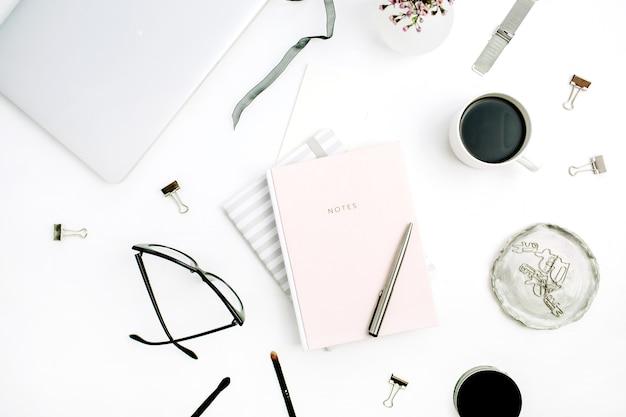 Scrivania da ufficio moderna da donna con quaderno rosa pastello, occhiali, tazza da caffè, fiori selvatici e accessori su sfondo bianco